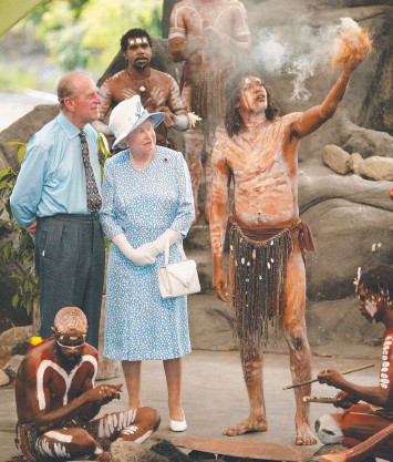 ??  ?? Prince Philip and Queen Elizabeth watch local indigenous performers light a ceremonial fire during a special cultural performance in Cairns in 2002.