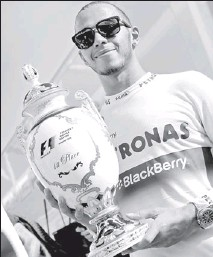 ??  ?? Mercedes Formula One driver Lewis Hamilton of Britain poses with his trophy after winning the Hungarian F1 Grand Prix at the Hungaroring circuit in Mogyorod, - REUTERS