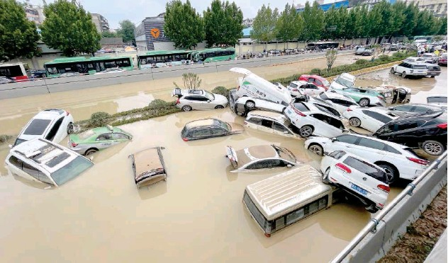 ?? Agence France-presse ?? ↑ Residents look at cars, caught in floodwaters, after heavy rain in Zhengzhou on Wednesday.
