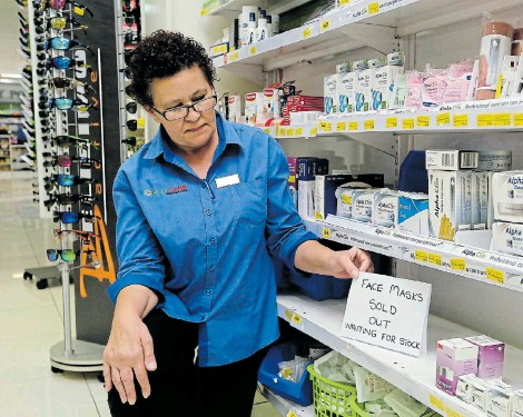?? Picture: WERNER HILLS ?? SOLD OUT: Klinimed Pharmacy stock assistant Veronica Niekerk at an empty shelf where face masks were kept in the Newton Park store. Gloves, goggles and thermometers were also selling out fast after the first coronavirus case in SA was confirmed