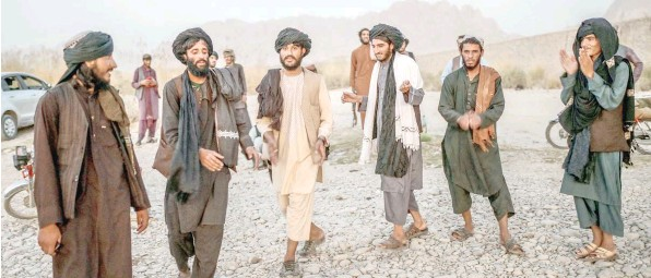?? — AFP ?? Taliban members enjoy a traditional dance on the banks of a river in Kandahar.