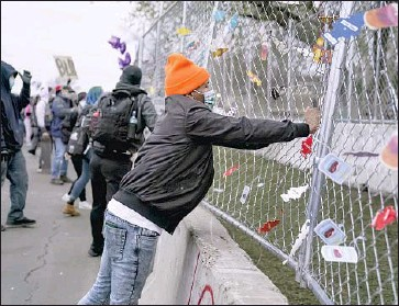 ?? Jason Armond Los Angeles Times ?? PROTESTERS hang car air fresheners on a fence outside the Brooklyn Center, Minn., police station. Daunte Wright, 20, was fatally shot after police pulled him over for having an air freshener on his rearview mirror.