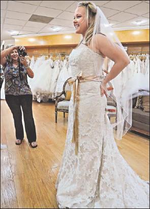 ?? By Robert Hanashiro, USA TODAY ?? Pinterest bride: Trish Smith tries on a wedding dress she found onlinevia Pinterest at Mary Me Bridal inOrange, Calif., as mom Phyllis Smithtakes a snapshot. Her wedding is setfor November.