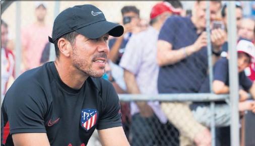 ??  ?? Simeone observa una sesión de entrenamiento de sus jugadores durante una pretemporada con la presencia de múltiples aficionados.
