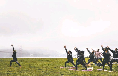 ?? Stephen Lam / The Chronicle ?? Outdoor Yoga SF instructor Kirin Power (left) leads a class of masked students at Crissy Field in San Francisco.
