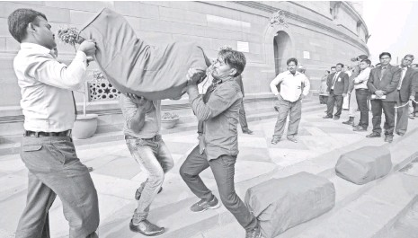?? MANISH SWARUP, AP ?? Indian workers in New Delhi struggle with the weight of a bag containing copies of the 2016-17 federal budget.