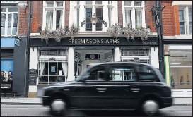 ??  ?? Un taxi londinense pasa por delante del histórico Freemasons Arms.