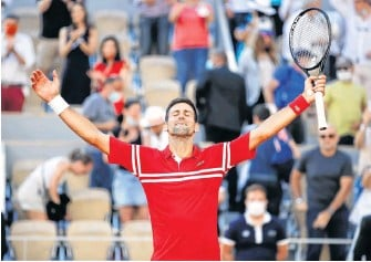 ?? GONZALO FUENTES • REUTERS ?? Serbia's Novak Djokovic celebrates after winning the French Open men's singles final against Greece's Stefanos Tsitsipas at Roland Garros in Paris on Sunday.