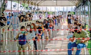 ??  ?? People sit in line to get their samples taken during a mass testing event at a sport complex in Bangkok after the recent outbreak of Covid-19 coronavirus cases in Thailand. — AFP photo