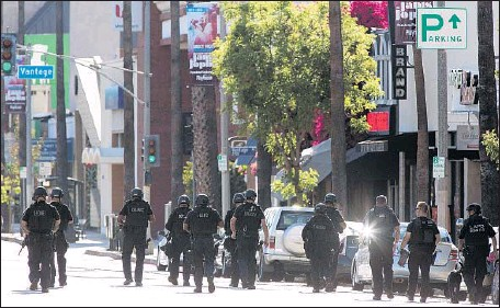 ?? Brian van der Brug Los Angeles Times ?? VENTURA BOULEVARD was closed for hours as investigators combed the scene after Los Angeles police shot and killed a man who fired a gun outside a bank. Witnesses took cover inside storefronts and behind cars as the incident unfolded, but no other...