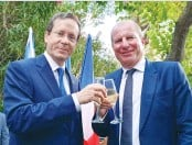 ?? (Courtesy Embassy of France) ?? PRESIDENT ISAAC HERZOG and Eric Danon, ambassador of France, clink glasses on Bastille Day.