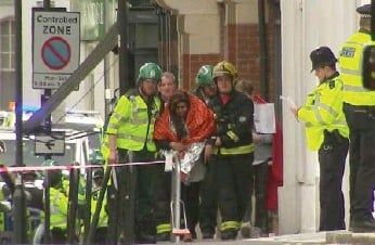 ?? SKY VIA THE ASSOCIATED PRESS ?? A woman is escorted to safety by emergency services near the scene of an explosion in London on Friday.