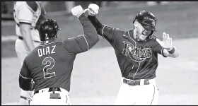 ?? Sean M. Haffey / Getty Images ?? The Rays' Michael Brosseau, right, celebrates with teammate Yandy Diaz after hitting a solo home run against the Yankees in the eighth inning of Game 5 of the ALDS at Petco Park in San Diego.