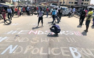 ?? PHOTO: REUTERS ?? A demonstrator paints ''End Sars'', referring to the Special AntiRobbery Squad police unit, on a street during a protest demanding police reform in Lagos.