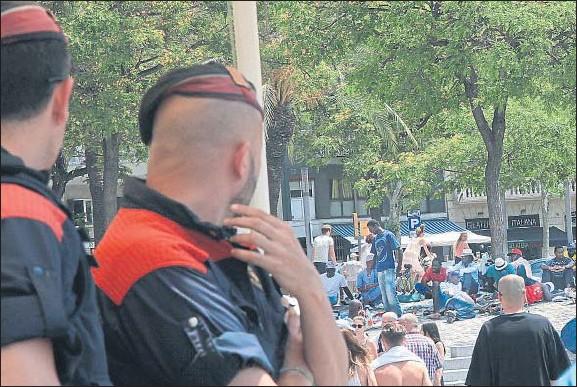 ?? KIM MANRESA ?? Unos mossos observan desde la zona del Palau de Mar las evoluciones de los manteros en el paseo Joan de Borbó sin intervenir