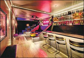 ??  ?? REACHED by a separate entrance, the lower-level lounge has a mirrored wet bar, a neon-lit wall and a nine-seat home theater.
