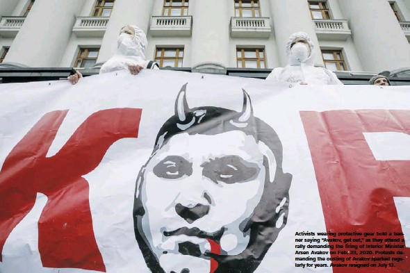 """??  ?? Activists wearing protective gear hold a banner saying """"Avakov, get out,"""" as they attend a rally demanding the firing of Interior Minister Arsen Avakov on Feb. 23, 2020. Protests demanding the ousting of Avakov sparked regularly for years. Avakov resigned on July 13."""