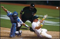 ?? JEFF CHIU — THE ASSOCIATED PRESS ?? The A's Matt Chapman, right, slides home to score past Dodgers catcher Will Smith during the ninth inning on Wednesday in Oakland.