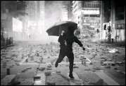 ?? KIN CHEUNG / ASSOCIATED PRESS ?? A protester with an umbrella runs from tear gas fired by riot police Monday on a street scattered with bricks during a protest in Hong Kong