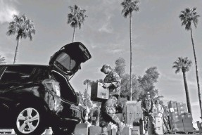 ?? MATT YORK/AP ?? Members of the Arizona National Guard distribute food last March in Mesa, Ariz. The Guard had been activated to bolster the supply chain and distribution of food amid surging demand in response to the coronavirus outbreak.