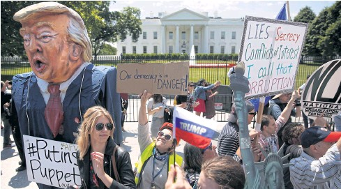?? REUTERS ?? Protesters rally against US President Donald Trump's firing of FBI director James Comey outside the White House in Washington, DC, on Wednesday.