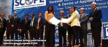 ??  ?? SHARALA (tengah, berbaju putih) bertukar dokumen dengan pegawai SCOPE.