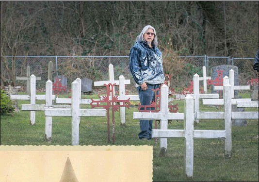 ?? ARLEN REDEKOP/PNG ?? Sto:lo historian Sonny Naxaxalhts'i McHalsie walks among crosses at Tzeachten First Nation graveyard in Chilliwack, one of the local cemeteries where children who died at Coqualeetza Residential School, left, were eventually buried.