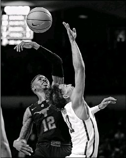 ?? Sue Ogrocki/The Associated Press ?? Texas' Kerwin Roach (12) bats the ball away from Oklahoma's Trae Young. Roach was the primary defender against Young, the nation's leader scoring, who had 26 points but hit just seven of 21 shots.