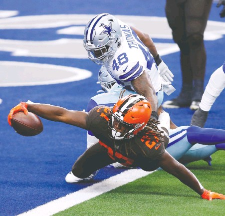 ?? TIM HEIT­MAN/ USA TO­DAY SPORTS ?? Cleve­land run­ning back Ka­reem Hunt dives for a touch­down against Dal­las line­backer Joe Thomas in the sec­ond quar­ter of Sun­day's NFL game at AT&T Sta­dium. The Browns jumped out to a big lead and then hung on for a 49-38 vic­tory.