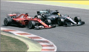 ?? PICTURE: REUTERS ?? Mercedes' Lewis Hamilton goes neck and neck with Ferrari's Sebastian Vettel at the Spanish Formula One Grand Prix yesterday. Hamilton took the victory, despite Vettel's valiant attempts to snatch back the lead.