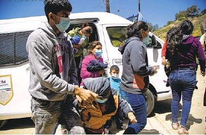 ?? ALEJANDRO TAMAYO U-T PHOTOS ?? A Mexican government van drops off asylum seekers at Templo Embajadores de Jesus on Thursday in Tijuana. The U.S. government has been expelling families to Mexico after flying them to San Diego.