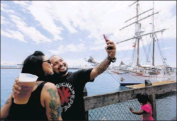 ?? Photographs by Francine Orr Los Angeles Times ?? JACKIE GOMEZ, left, and Eddie Tapia take a selfie at the San Pedro Fish Market, which first opened in 1957. A planned development at nearby Ports O' Call Village has owner Tommy Amalfitano concerned.
