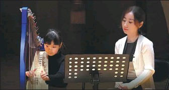 ?? PROVIDED TO CHINA DAILY ?? Harpist Wang Guan (right) teaches during the annual music training program, Gateway to Music, in the summer of 2020.