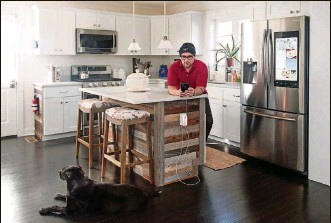 ?? MONICA JORGE/THE NEW YORK TIMES ?? Chris Petrock at home, where he adjusts the settings of his kitchen's smart devices via his iPhone, in Norwalk, Conn., Jan. 11. 59 percent of American adults surveyed in 2018 said they were interested in using a smart home device, according to Forrester Research.