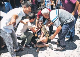 ?? AP ?? People help a victim at the site where an explosion killed over 30 and injured scores in the southeastern Turkish city of Suruc, near the Syrian border, on Monday.