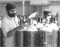?? Aijaz Rahi/the Associated Press ?? A worker at a gas supply facility in Bengaluru checked oxygen cylinders before they were delivered to hospitals. India has reported a new record 295,041 coronavirus cases as the daily death toll crossed 2,000 for the first time.
