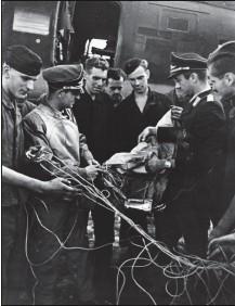 ?? DR/COLL. CHRIS GOSS ?? Franz Vuellers (deuxième en partant de la gauche) et son staffel kapitän (en face) inspectent câble et parachute accrochés à l'avion.