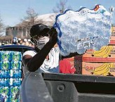 ?? Brett Coomer / Staff photograph­er ?? Eunice Russ loads a case of water Tuesday during a food distributi­on event at NRG Stadium.