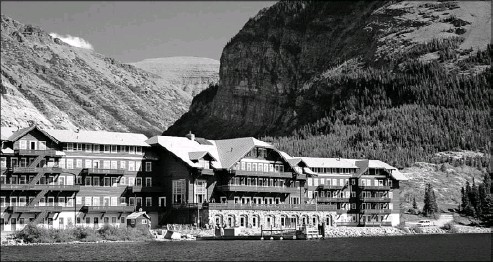 ?? Patti Pfeiffer ?? Situated between four mountain peaks, the Many Glacier Hotel overlooks the waters of glacier-fed Swiftcurrent Lake in Glacier National Park.