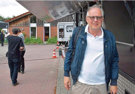 ?? FOTOS: SVEN TIETGEN ?? Axel Milberg willigte gern in ein Foto vor dem Drehpausen-Snack am Dorfgemeinschaftshaus ein.