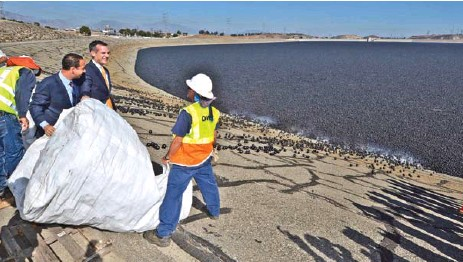 """??  ?? Los Angeles Mayor Eric Garcetti dumps a bag of """"Shade balls"""" into the L.A. reservoir in August 2015."""