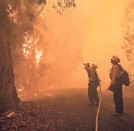 ?? PHILIP PACHECO/AFP VIA GETTY IMAGES ?? Firefighters battle the Kincade Fire along Chalk Hill Road in Healdsburg, Calif., on Sunday.