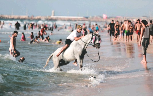 ?? PHOTOS BY LOAY AYYOUB FOR THE WASHINGTON POST ?? A man rides a horse along the Mediterranean shore in the Gaza Strip, where many have stopped swimming in the sea because of pollution from untreated sewage.