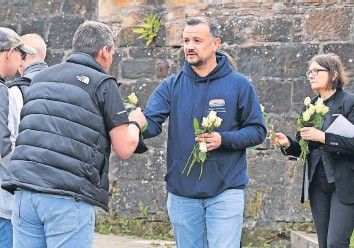 ??  ?? Symbol of remembrance Handing out roses to take to the canal