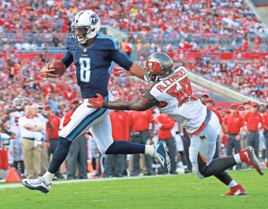 ?? KIM KLEMENT, USA TODAY SPORTS ?? Quarterback Marcus Mariota runs past Bucs linebacker Kwon Alexander during the first half of the Titans' 42-14 victory in Tampa.
