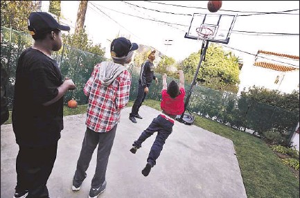 """?? Photographs by Barbara Davidson Los Angeles Times ?? CHILDREN RARELY go outside at the Door of Hope homeless center for security reasons, making the new basketball court that much more special. """"For kids going through trauma, to be able to do kid things, that's such a big thing,"""" said one official."""