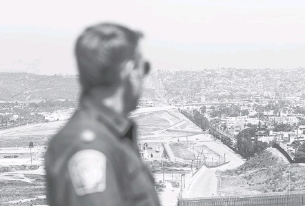 ?? CAROLYN VAN HOUTEN/THE WASHINGTON POST ?? Rodney Scott, chief of the Border Patrol's San Diego sector, looks out toward Tijuana, Mexico, in April as some of his agents respond to a call in the distance. Many of the year's false claims related to the U.S.-Mexico border and the migrant caravan that approached it this fall.