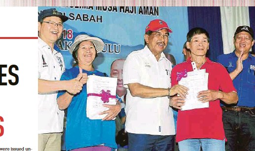 ?? LAN PIX BY LANO ?? Sabah Chief Minister Tan Sri Musa Aman (centre) presenting land titles to beneficiaries of the Sabah Native Land Services programme in Kiulu yesterday. With him are Tuaran member of parliament Datuk Seri Wilfred Madius Tangau (left) and Kiulu...