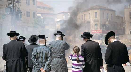 ?? THE ASSOCIATED PRESS ?? Ultra-Orthodox Jewish men and children burn leavened items in final preparation for the Passover holiday in Jerusalem, Friday.