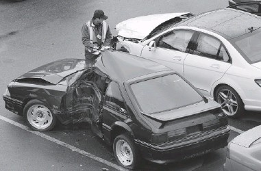 ?? NICK PROCAYLO/ PNG FILES ?? A worker examines a car at the ICBC's damaged vehicle lot at the south end of the Queensborough Bridge in Richmond. A new book exposes aspects of the way the ICBC deals with claimants that might surprise the average reader.